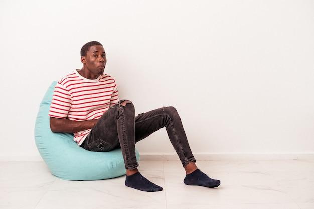 Il giovane afroamericano seduto su un puff isolato su sfondo bianco alza le spalle e apre gli occhi confusi.