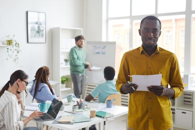 Giovane uomo afro-americano e sorridente con business team multietnico