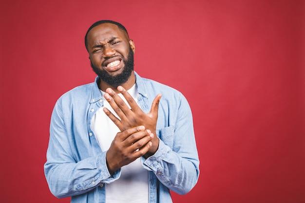 Dolore di sofferenza del giovane uomo afroamericano sulle mani e sulle dita, infiammazione di artrite. isolato su rosso.