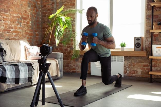 Giovane afroamericano che insegna a casa corsi online di fitness