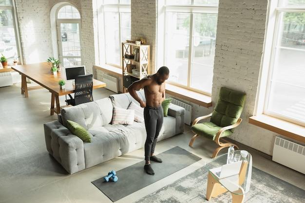Giovane uomo afroamericano che si allena a casa durante la quarantena dell'epidemia di coronavirus,