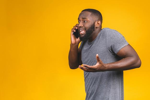 Giovane uomo afroamericano che per mezzo dello smartphone sollecitato, colpito dalla vergogna e dalla faccia di sorpresa, arrabbiato e frustrato. paura e turbamento per errore.