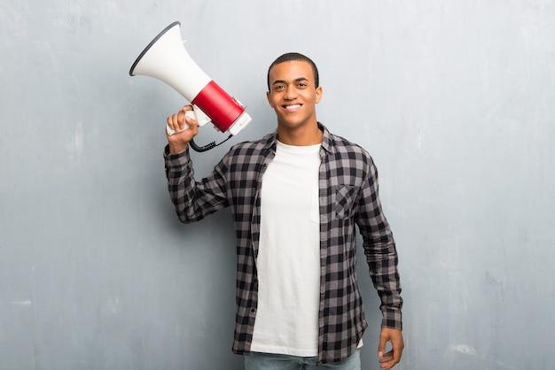 Giovane uomo afroamericano con la camicia a quadretti che tiene un megafono
