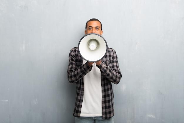 Giovane uomo afroamericano con la camicia a quadretti che grida tramite un megafono per annunciare qualcosa