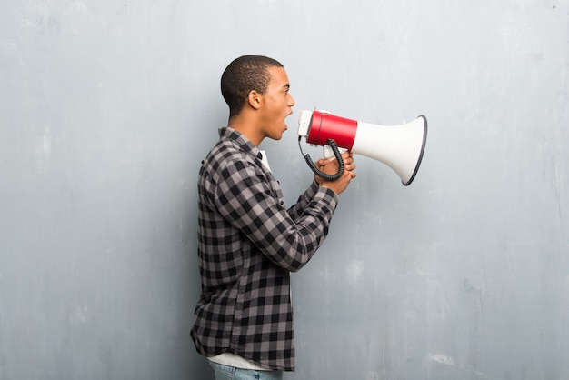 Giovane uomo afroamericano con la camicia a quadretti che grida tramite un megafono