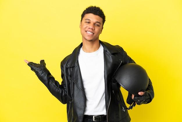 Giovane uomo afroamericano con un casco da motociclista isolato su sfondo giallo che estende le mani di lato per invitare a venire