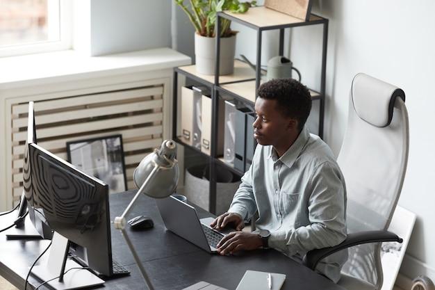 Giovane uomo afroamericano che lavora in ufficio