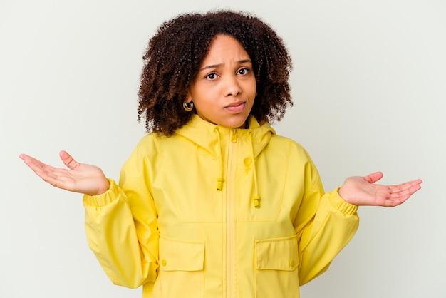 Giovane donna afroamericana di razza mista isolata dubitando e scrollando le spalle nel gesto interrogativo.