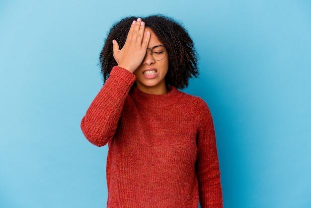 Giovane donna afroamericana di razza mista isolata dimenticando qualcosa, schiaffeggiando la fronte con il palmo e chiudendo gli occhi.