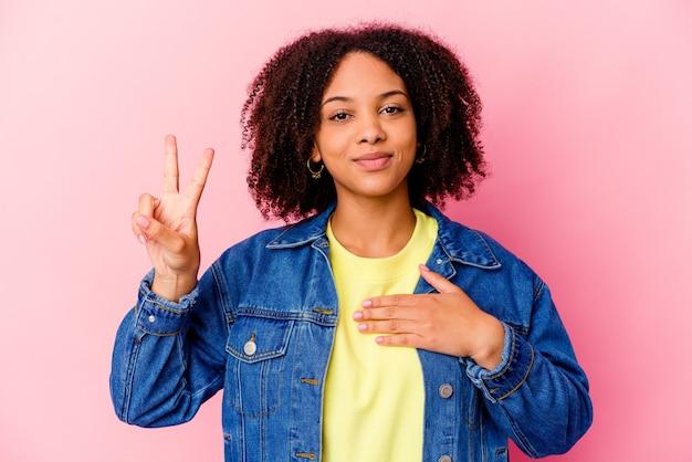 Giovane donna afroamericana di razza mista isolata prestando giuramento, mettendo la mano sul petto.