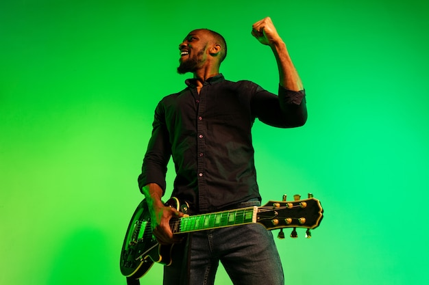 Giovane musicista afroamericano che suona la chitarra come una rockstar su sfondo verde-giallo sfumato. concetto di musica, hobby, festival, open-air. ragazzo allegro che improvvisa, canta una canzone.
