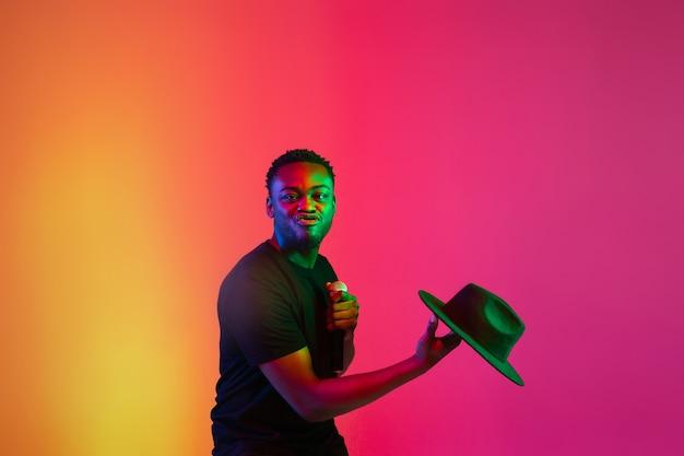 Giovane musicista afroamericano che canta su sfondo sfumato arancio-viola per studio alla luce al neon. concetto di musica, hobby, festival. ospite gioioso della festa, alzati in piedi. ritratto colorato dell'artista.