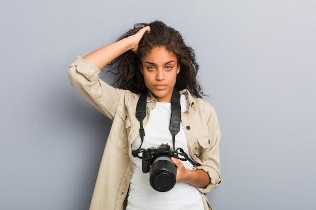 Giovane donna afro-americana fotografo con in mano una macchina fotografica scioccata, ha ricordato un incontro importante.