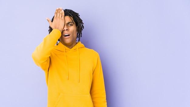 Giovane uomo rasta afroamericano dimenticando qualcosa, schiaffi sulla fronte con il palmo e chiudendo gli occhi.