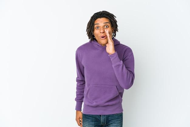 Il giovane uomo rasta afroamericano sta dicendo una notizia segreta di frenata calda e sta guardando da parte