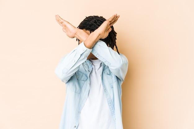 Giovane uomo afroamericano rasta mantenendo due braccia incrociate, concetto di negazione.