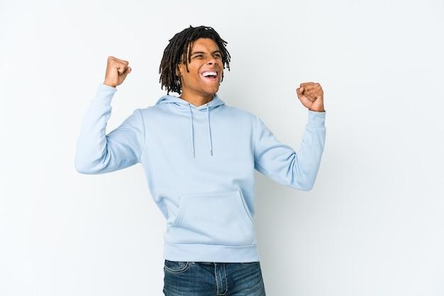Giovane uomo rasta afroamericano che alza il pugno dopo una vittoria, concetto di vincitore.