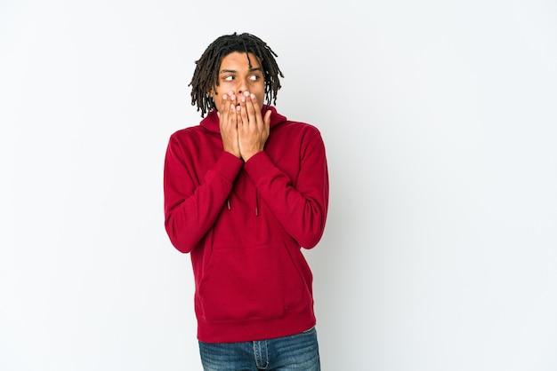 Giovane uomo rasta afroamericano premuroso guardando uno spazio di copia che copre la bocca con la mano.