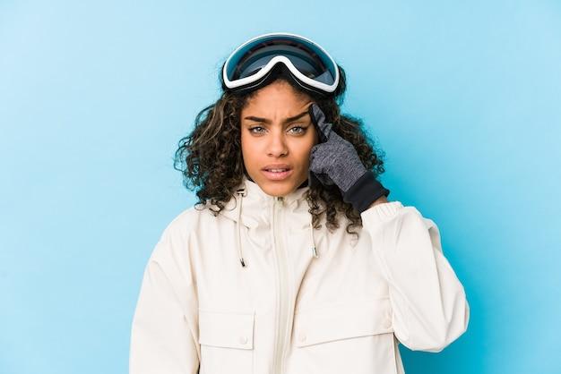 Donna giovane sciatore afroamericano isolata che mostra un gesto di delusione con l'indice.