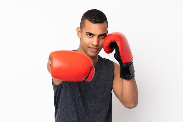 Giovane uomo afroamericano di sport sopra la parete bianca isolata con i guantoni da pugile