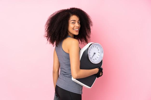Giovane donna afroamericana di sport isolata sul rosa con la pesa