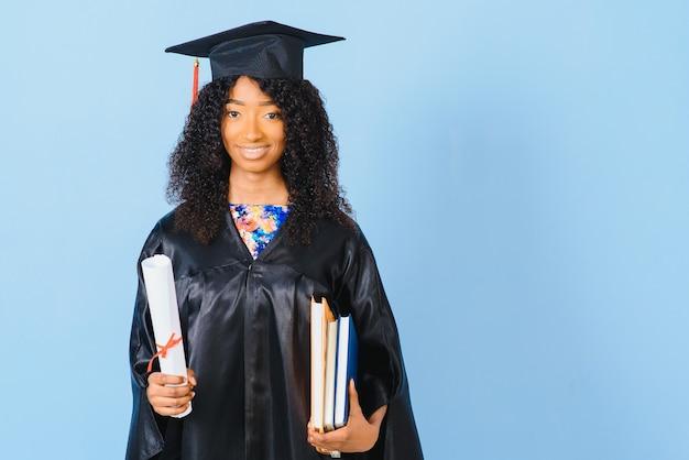 Giovane studente afro-americano in abito da scapolo su sfondo di colore