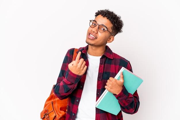 Uomo riccio giovane studente afroamericano che tiene i libri che puntano con il dito contro di te come se invitando ad avvicinarsi.