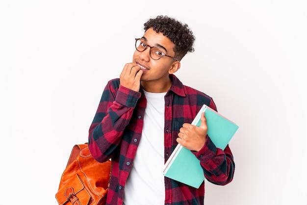 Uomo riccio giovane studente afroamericano isolato in possesso di libri unghie mordaci, nervoso e molto ansioso.
