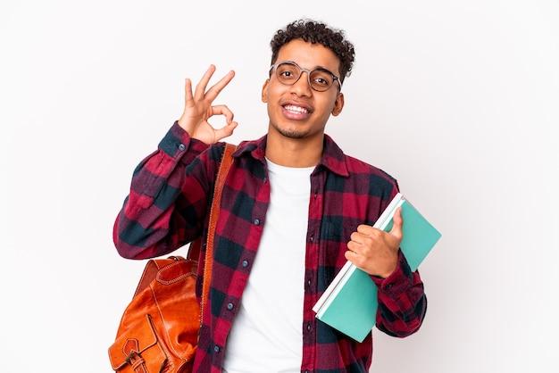 Il giovane uomo riccio dello studente afroamericano ha isolato i libri della tenuta allegro e sicuro che mostra gesto giusto