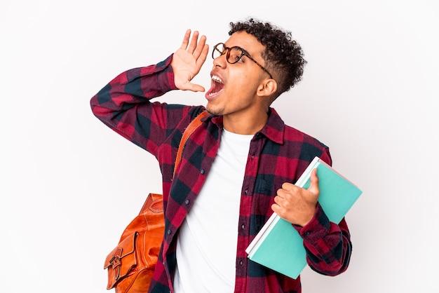 Uomo riccio giovane studente afroamericano isolato in possesso di libri gridando e tenendo il palmo vicino alla bocca aperta.