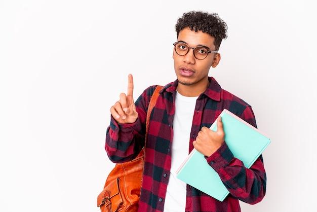 L'uomo riccio giovane studente afroamericano ha isolato i libri della holding che mostrano il numero uno con il dito.
