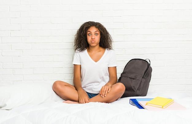 La giovane donna afroamericana studentessa sul letto soffia sulle guance, ha un'espressione stanca. concetto di espressione facciale.
