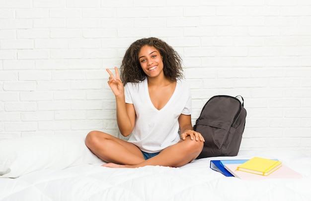Giovane donna afroamericana studentessa sul letto gioiosa e spensierata che mostra un simbolo di pace con le dita.