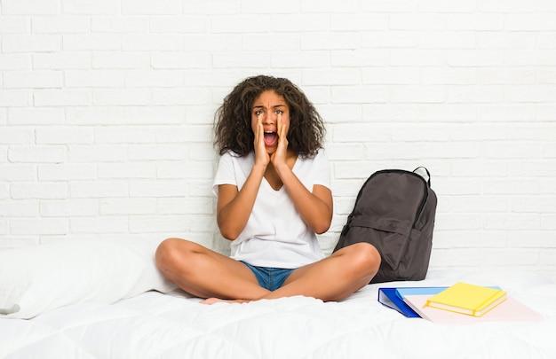 Giovane donna afroamericana dell'allievo sul letto che grida eccitato alla parte anteriore.