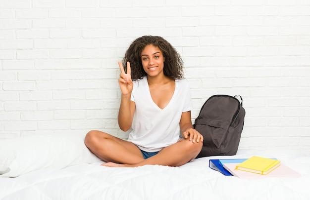 Donna giovane studente afroamericano sul letto che mostra il numero due con le dita.