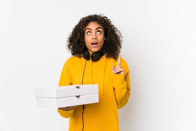 Donna giovane studente afroamericano che tiene le pizze che punta verso l'alto con la bocca aperta.