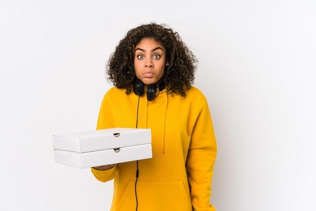 La giovane donna afroamericana dell'allievo che tiene le pizze alza le spalle e gli occhi aperti confusi.