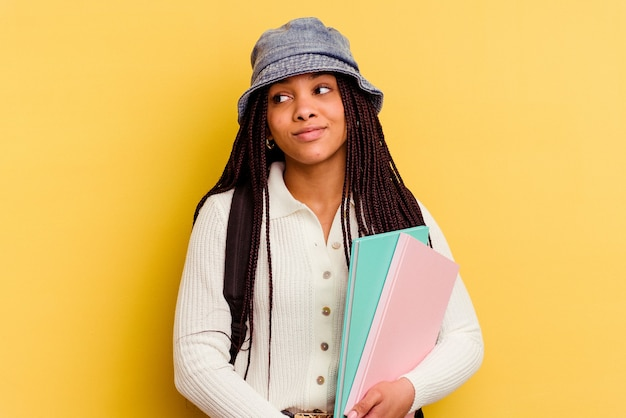 Donna giovane studentessa afroamericana isolata su giallo sognando di raggiungere obiettivi e scopi