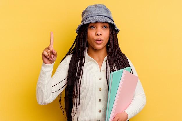 Giovane donna afroamericana studentessa isolata sulla parete gialla che ha qualche grande idea, concetto di creatività.