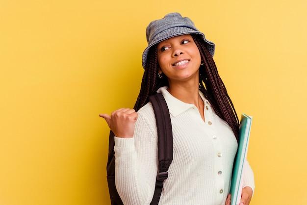 La giovane donna afroamericana dello studente isolata sui punti gialli della parete con il dito del pollice via, ridendo e spensierata.