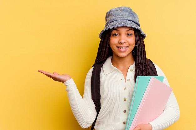 Donna giovane studentessa afroamericana isolata sulla parete gialla che mostra uno spazio della copia su una palma e che tiene un'altra mano sulla vita.
