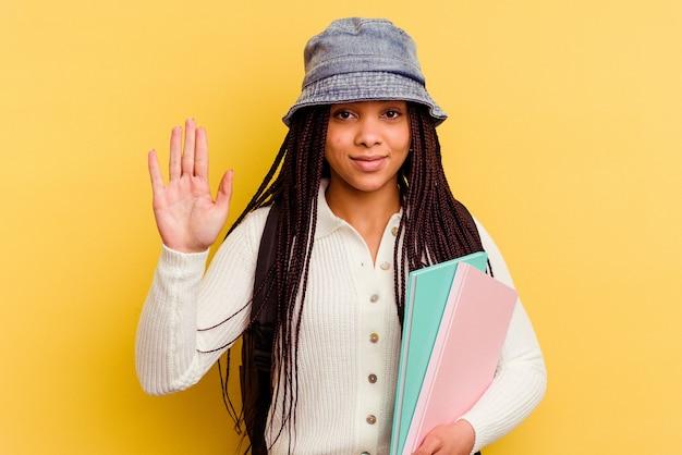 Giovane donna afroamericana studentessa isolata sul muro giallo sorridente allegro che mostra il numero cinque con le dita