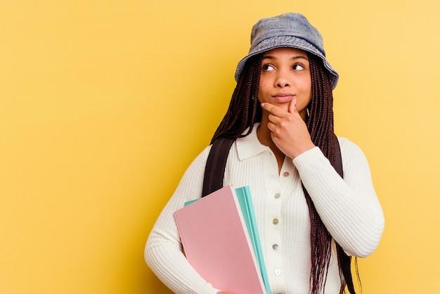 Donna giovane studente afroamericano che guarda lateralmente con espressione dubbiosa e scettica.