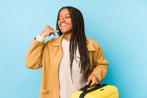 Donna giovane viaggiatore afroamericano che tiene una valigia isolata che mostra un gesto di chiamata di telefono cellulare con le dita.