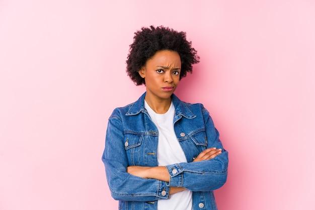 Giovane donna afroamericana contro un backgroound rosa isolato infelice guardando a porte chiuse con espressione sarcastica.