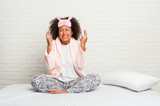 Giovane donna afroamericana nel letto che indossa le dita dell'incrocio del pigiama per avere fortuna