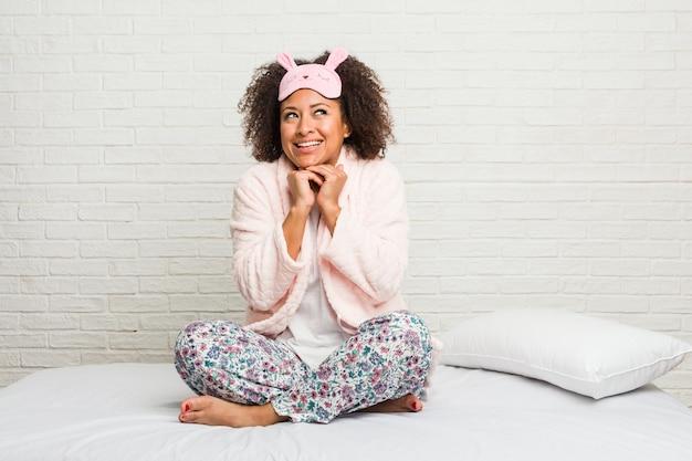 La giovane donna afroamericana nel letto che indossa il pigiama tiene le mani sotto il mento, sta guardando felicemente da parte.