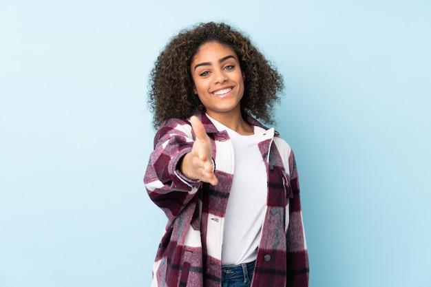 Giovane donna afro-americana sulla parete blu si stringono la mano per chiudere un buon affare