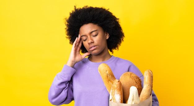 Giovane donna afro-americana che compra qualcosa di pane isolato con mal di testa