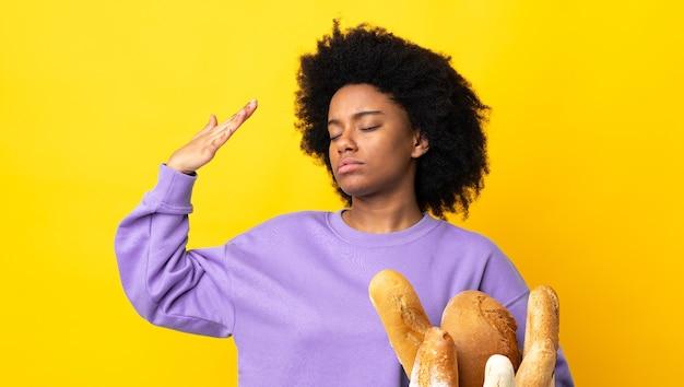 Giovane donna afro-americana che compra qualcosa di pane isolato su sfondo giallo con espressione stanca e malata